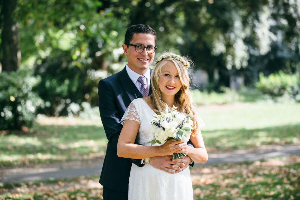 groom holding bride in Clissold Park natural wedding photos