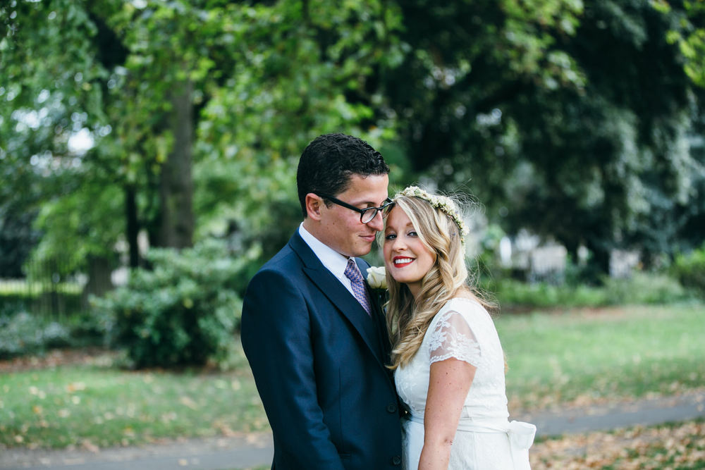 bride cuddling groom natural wedding portrait in Clissold Park