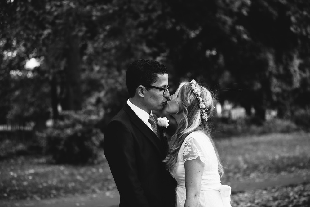 groom kissing bride Clissold Park wedding
