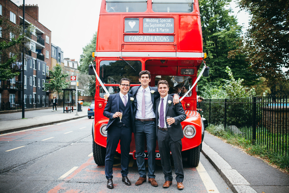 groom in front of red wedding bus Clissold newly married couple walking through Clissold Park Stoke Newington