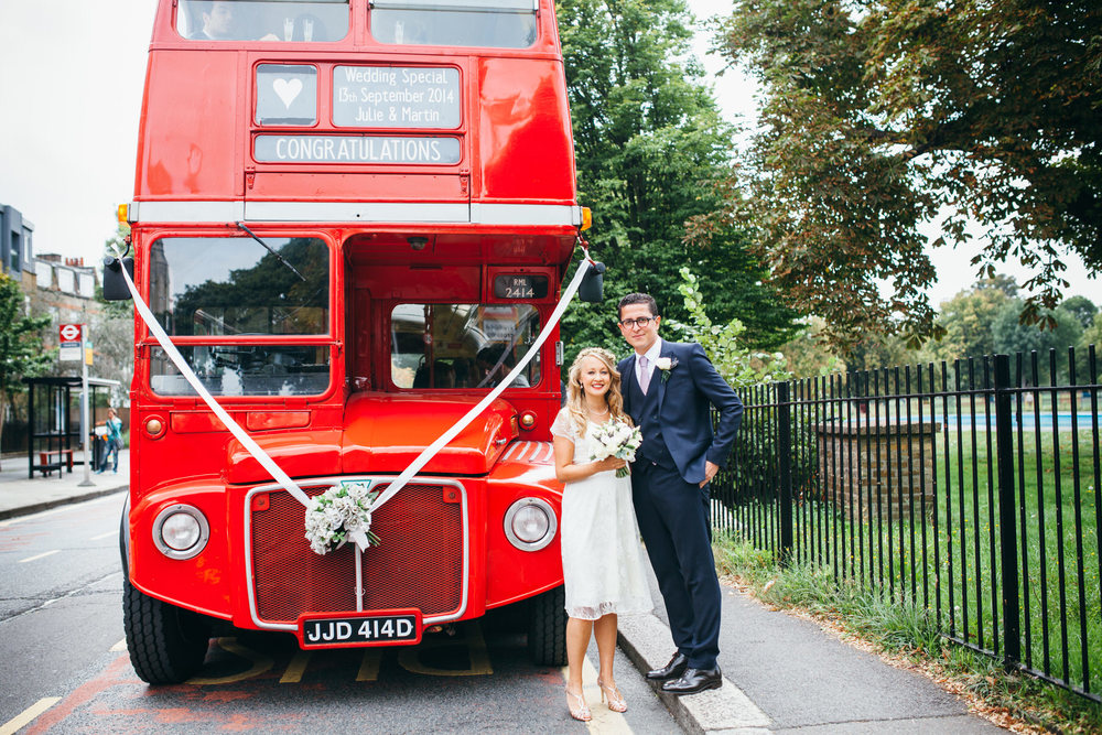 bride standing with groom red London wedding bus