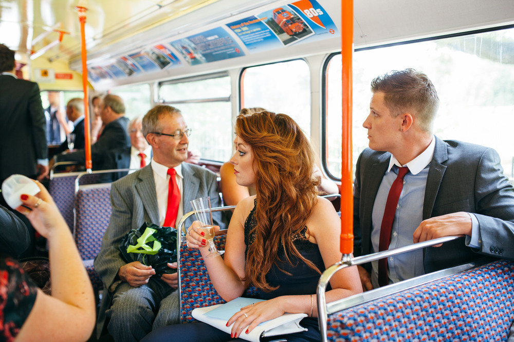 guests on red London wedding bus documentary photography