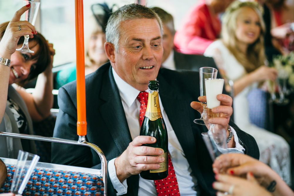 guests drinking French champagne red London wedding bus