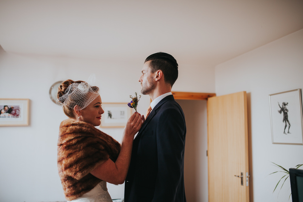 MS-Londesborough-Pub-wedding-Hackney-alternative-photographer-4-bride-placing-wildflower-boutoneire-on-groom.jpg