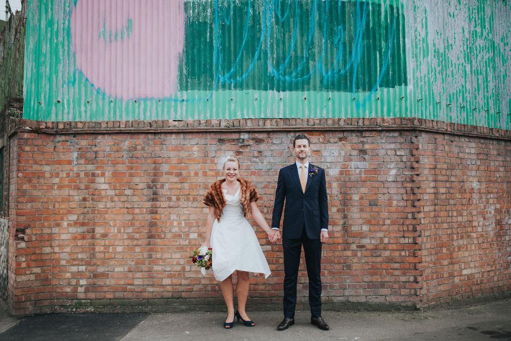 MS-Londesborough-Pub-wedding-Hackney-alternative-photographer-50-quirky-bride-groom-holding-hands-against-urban-grafitti-wall-London.jpg
