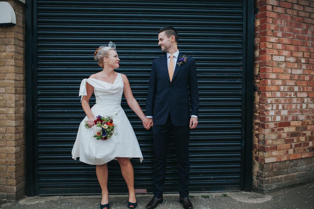 MS-Londesborough-Pub-wedding-Hackney-alternative-photographer-51-bride-wearing-Vivienne-Westwood-wedding-dress-looking-groom-black-metal-background.jpg