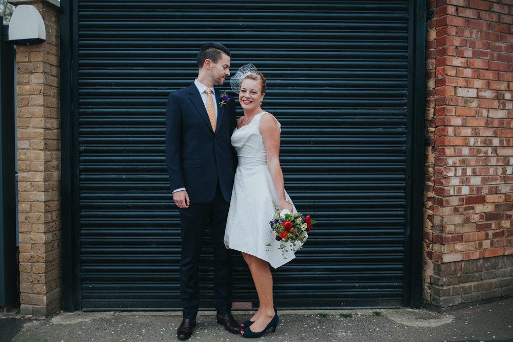 MS-Londesborough-Pub-wedding-Hackney-alternative-photographer-52-bride-wearing-Vivienne-Westwood-wedding-dress-looking-groom-black-metal-background.jpg