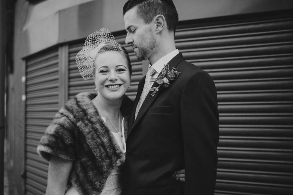 MS-Londesborough-Pub-wedding-Hackney-alternative-photographer-58-BW-bride-wearing-fur-stole-over-wedding-dress-kissing-groom-grey-metal-background.jpg