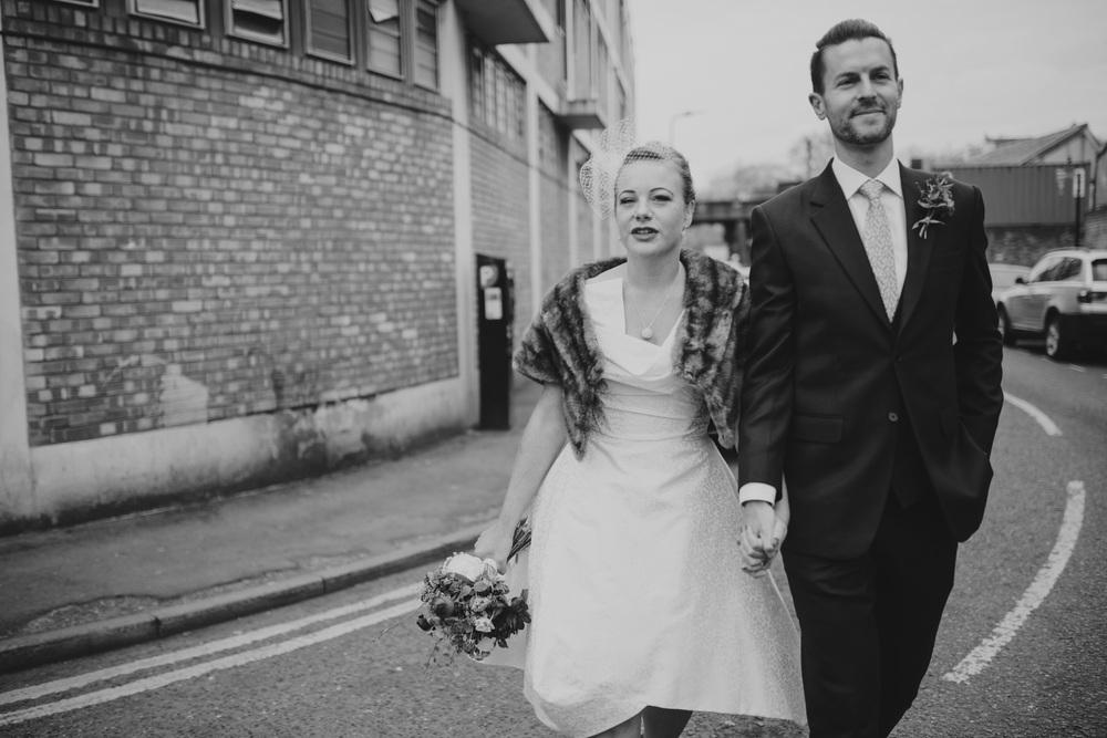 MS-Londesborough-Pub-wedding-Hackney-alternative-photographer-61-BW-bride-wearing-fur-stole-over-wedding-dress-walking-groom-reportage.jpg