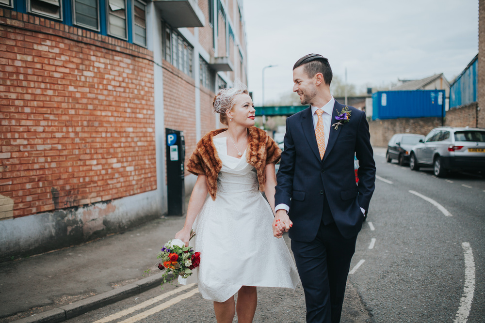 MS-Londesborough-Pub-wedding-Hackney-alternative-photographer-59-bride-wearing-fur-stole-over-wedding-dress-walking-groom-reportage.jpg