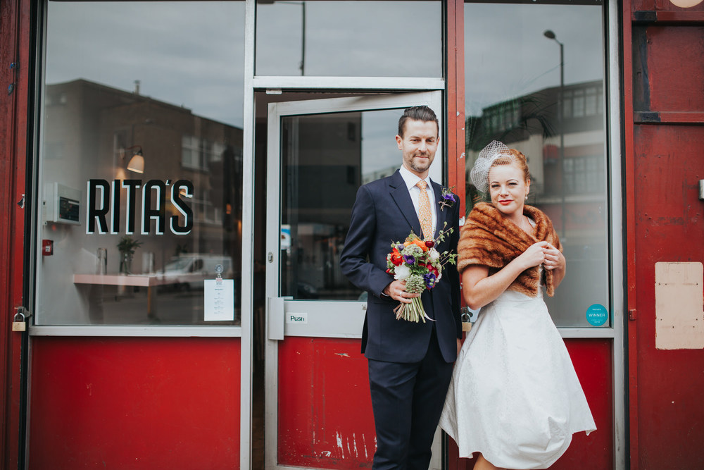 MS-Londesborough-Pub-wedding-Hackney-alternative-photographer-69-groom-outside-Ritas-holding-bouquet-bride-fur-stole.jpg