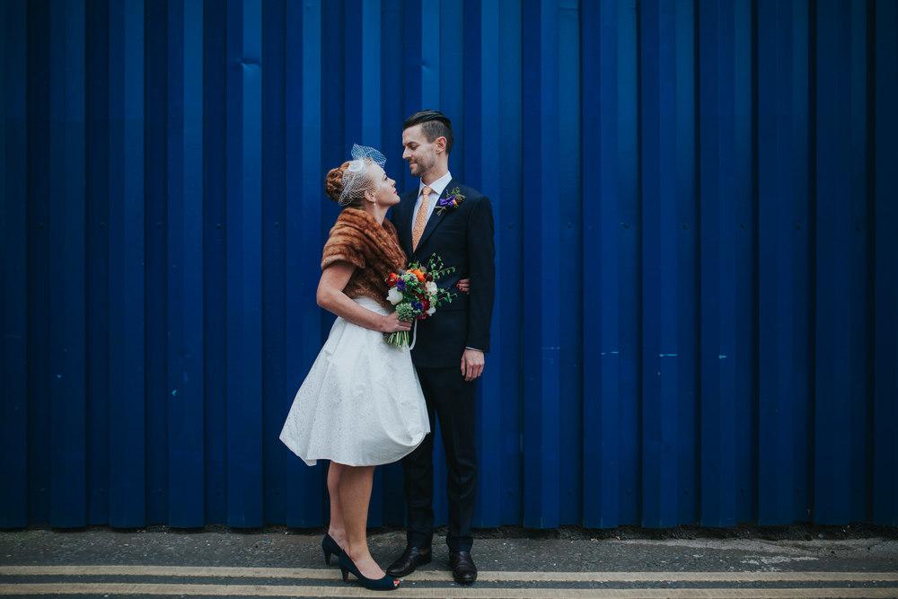 MS-Londesborough-Pub-wedding-Hackney-alternative-photographer-76-bright-blue-metal-background-urban-wedding-portrait-bride-groom-under-railway-bridge.jpg