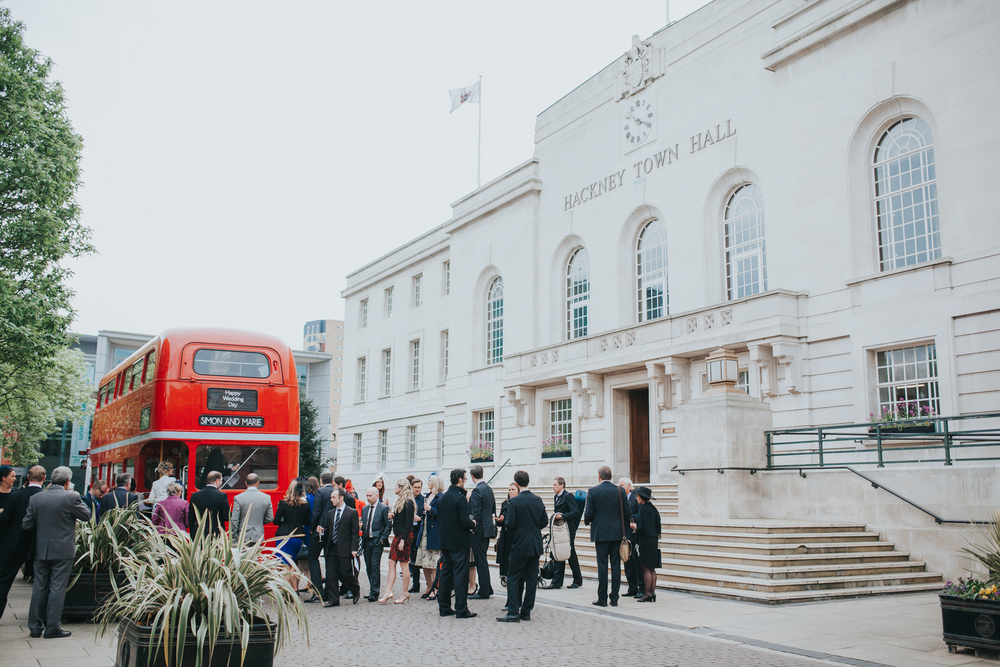 MS-Londesborough-Pub-wedding-Hackney-alternative-photographer-138-guests-drinking-bubbly-red-london-wedding-bus.jpg
