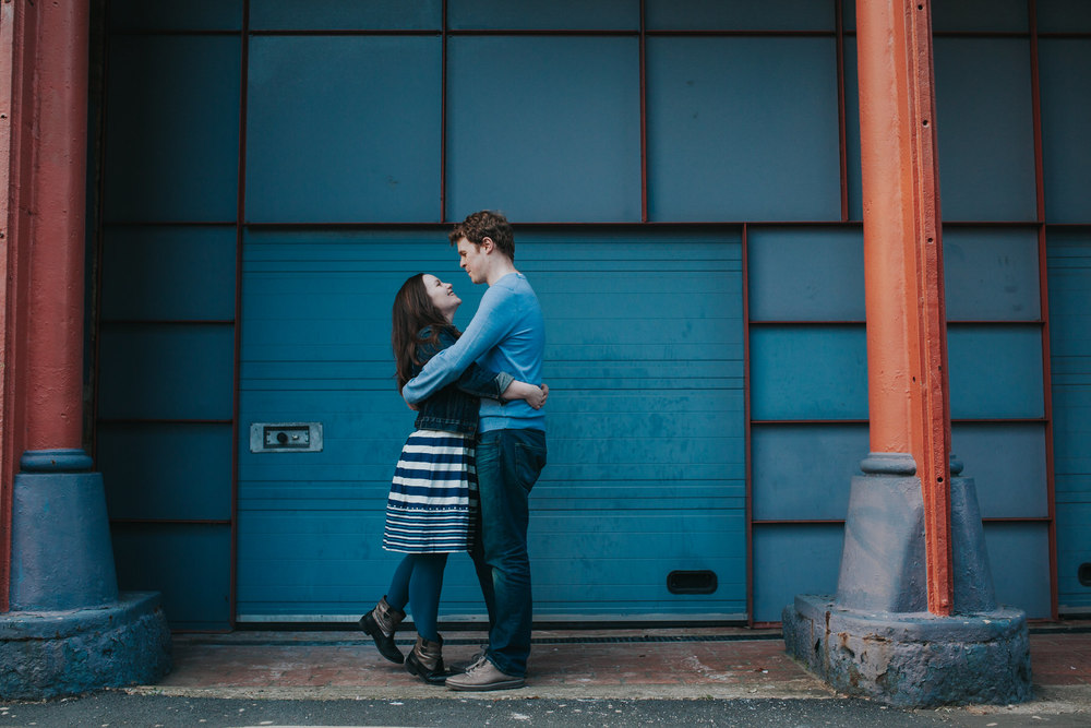 65-Quirky-engagement-London-couple-embracing-blue-background.jpg