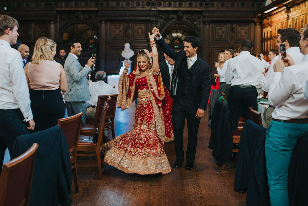 176-Anglo-Asian-Wedding-groom-leading-bride-red-sari.jpg
