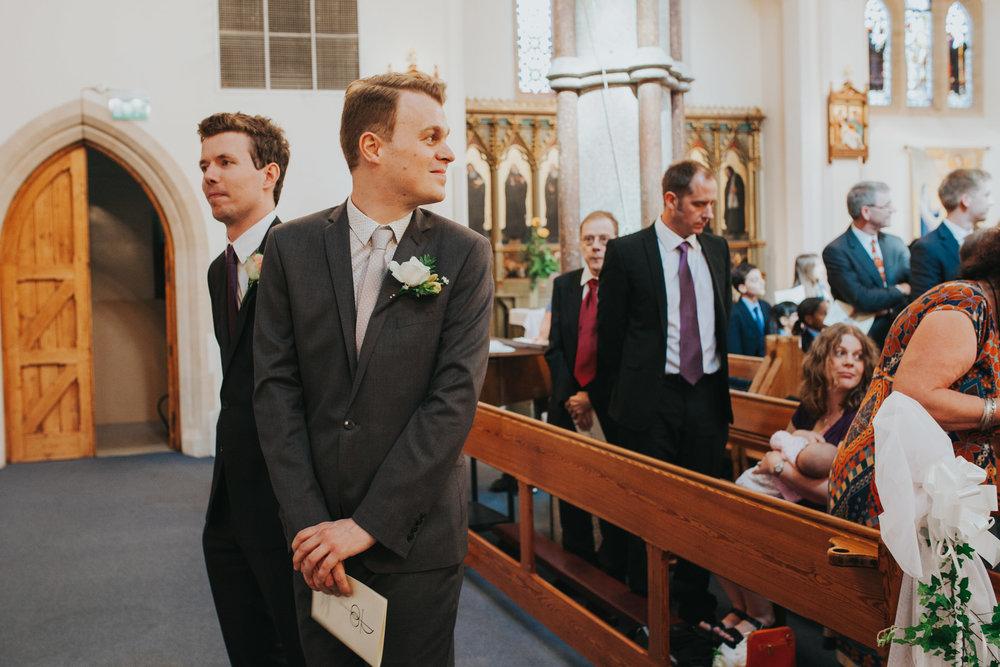 23 groom looking back down aisle Fulham Catholic Church wedding.jpg