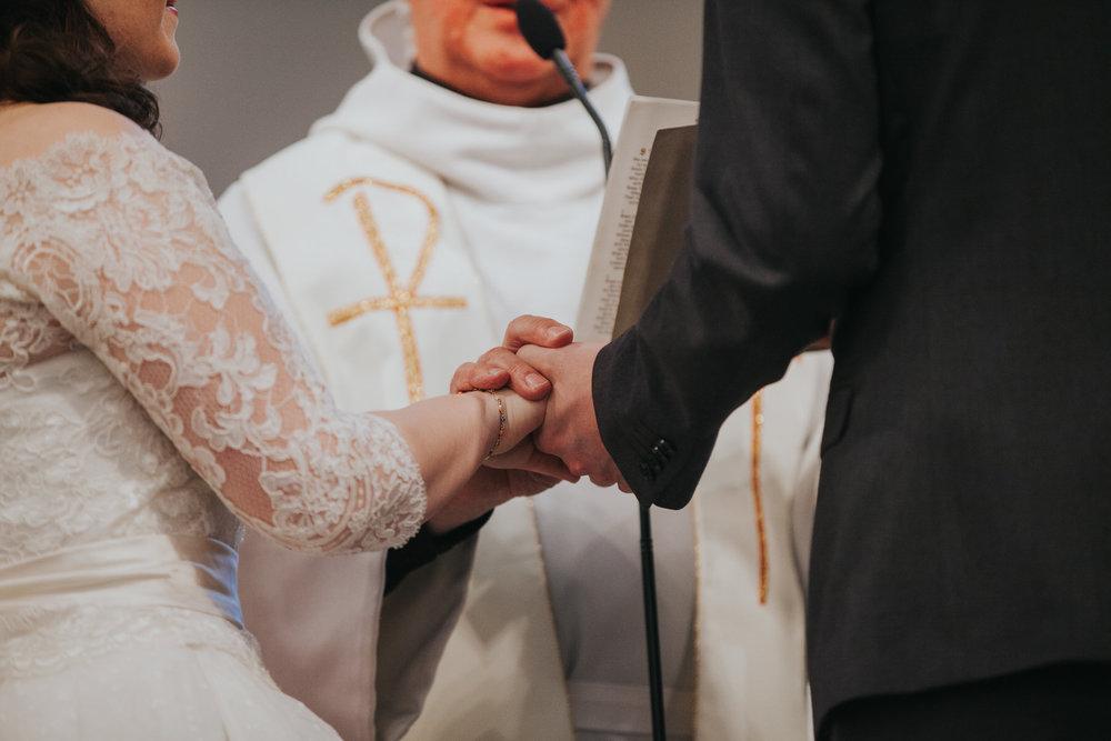 51 groom bride hands during Catholic Church wedding.jpg