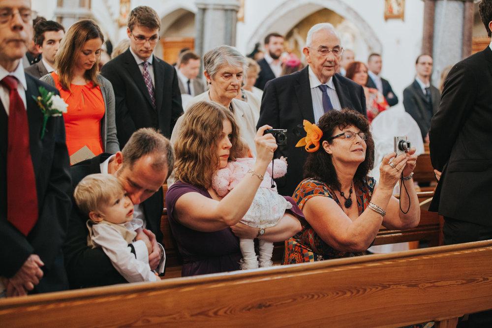 59 grooms family taking photos during Catholic Church wedding.jpg