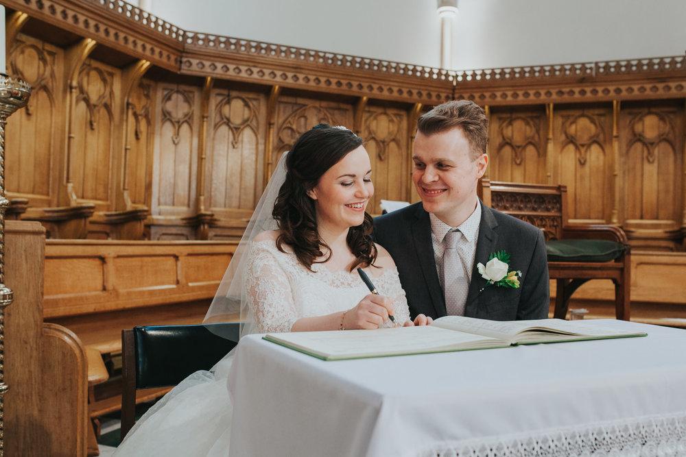 65 bride groom signing register Catholic Church wedding.jpg