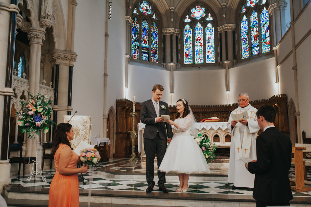 70 newly married couple signing Church wedding.jpg