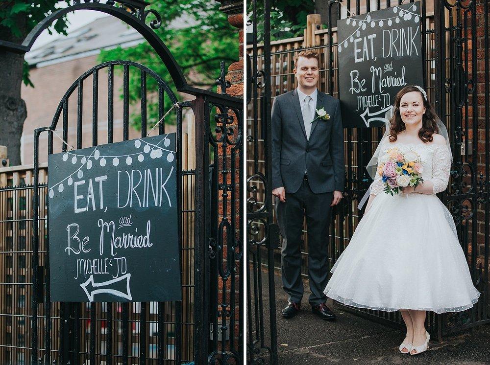 192 eat drink be married entrance sign bride groom arrive schoolyard wedding reception.jpg