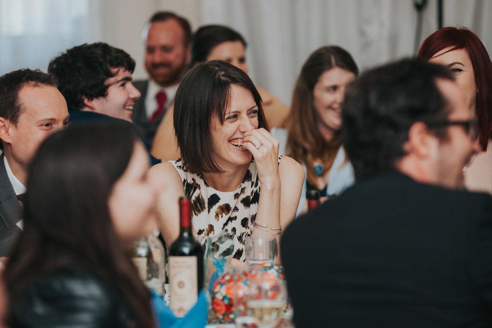 241 female guest laughing best mans speech school hall wedding.jpg