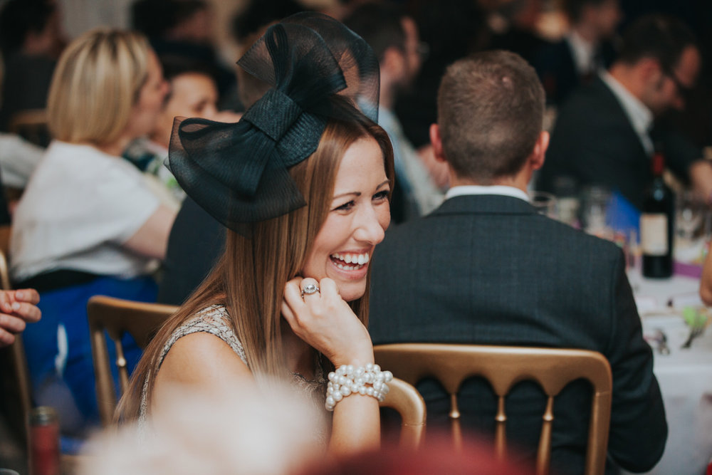 243 female guest laughing best mans speech school hall wedding London.jpg