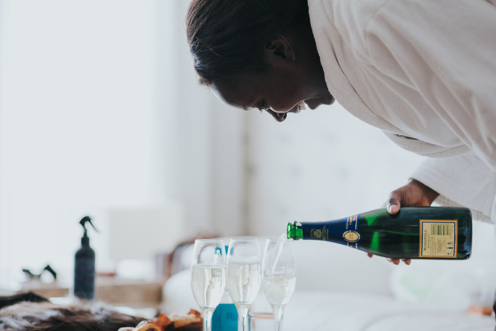 3-bride pouring champagne bridal preparations.jpg