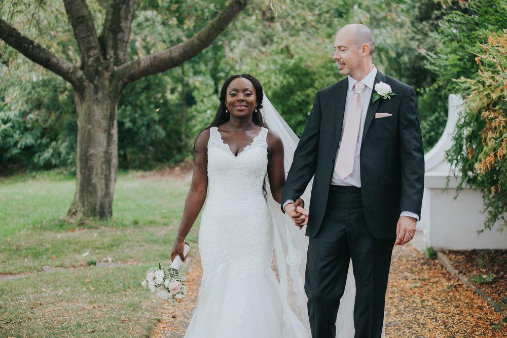 171 Dulwich wedding groom holding brides hand bridal photos.jpg