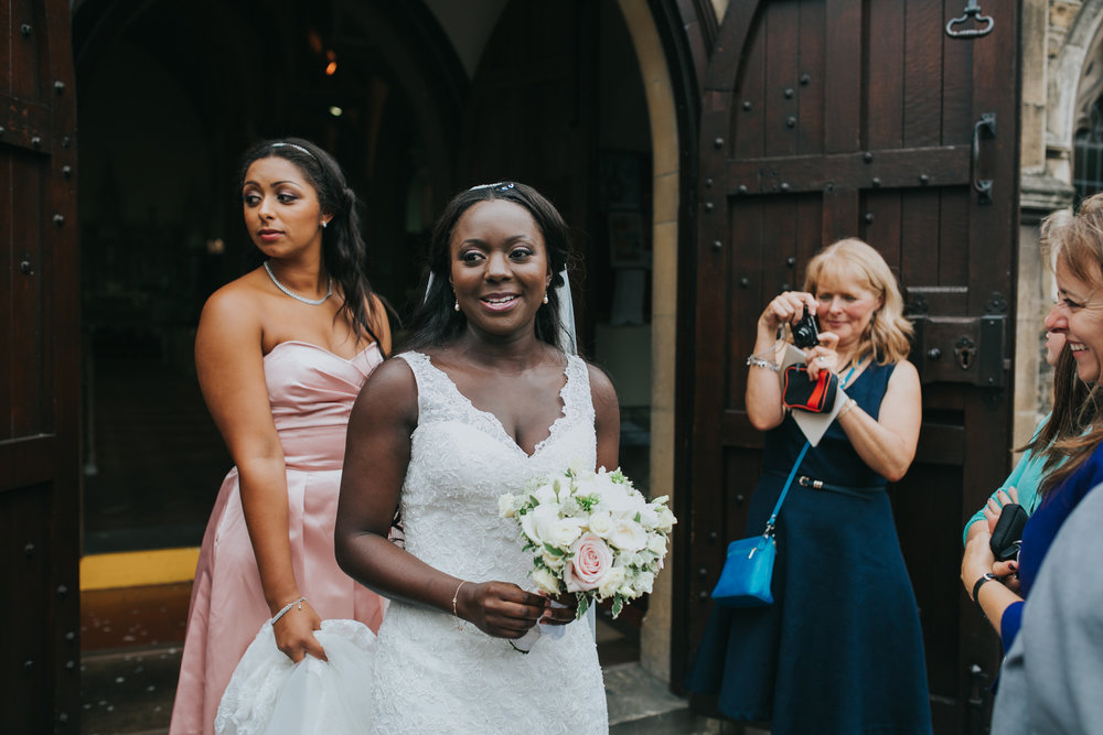 126 bridesmaid holding brides train Church wedding.jpg