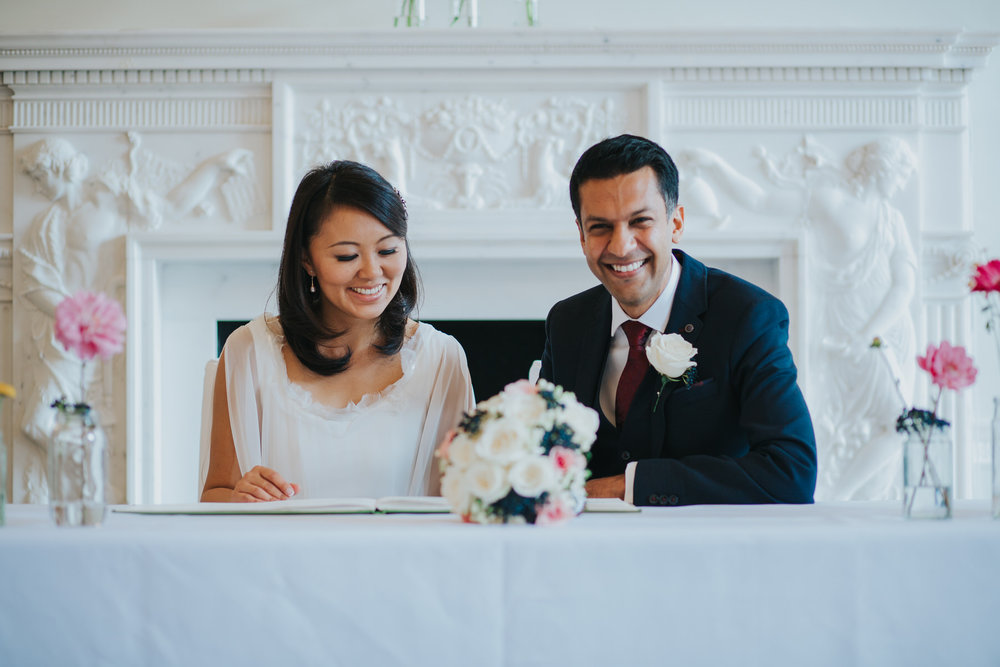 groom signs register Asia House with bride