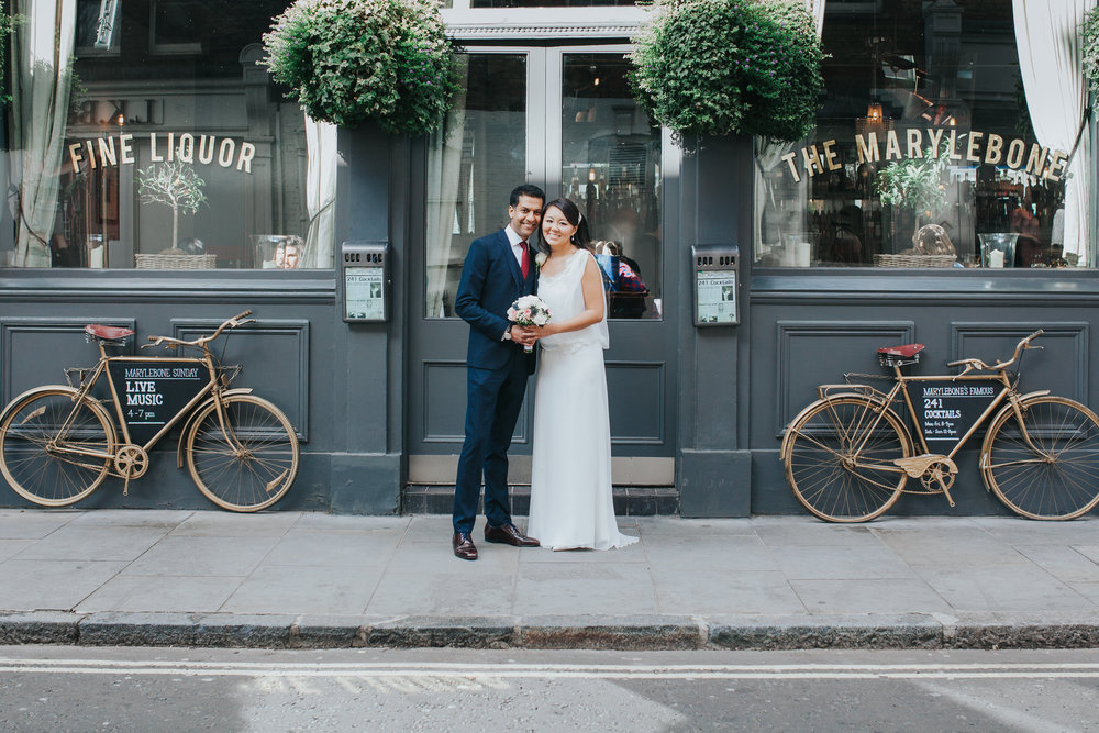 wedding couple outside The Marylebone gold bicycles