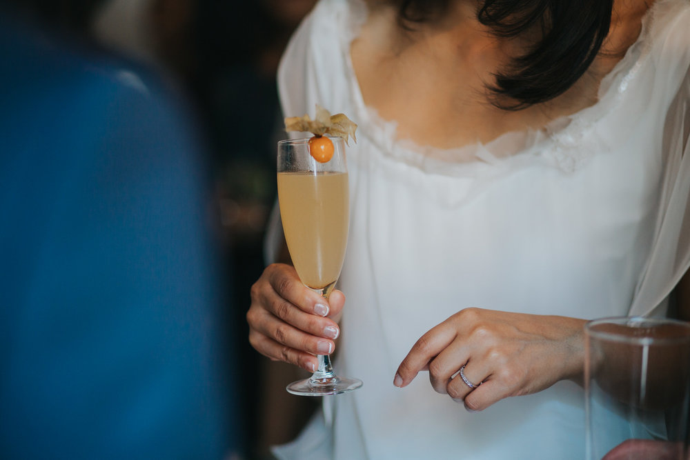 bride holding champagne cocktail phsyliis garnish