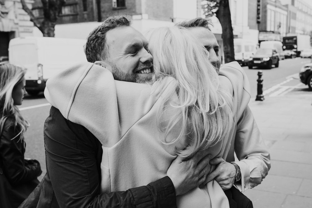 18 mother hugs both grooms Chelsea Town Hall wedding.jpg