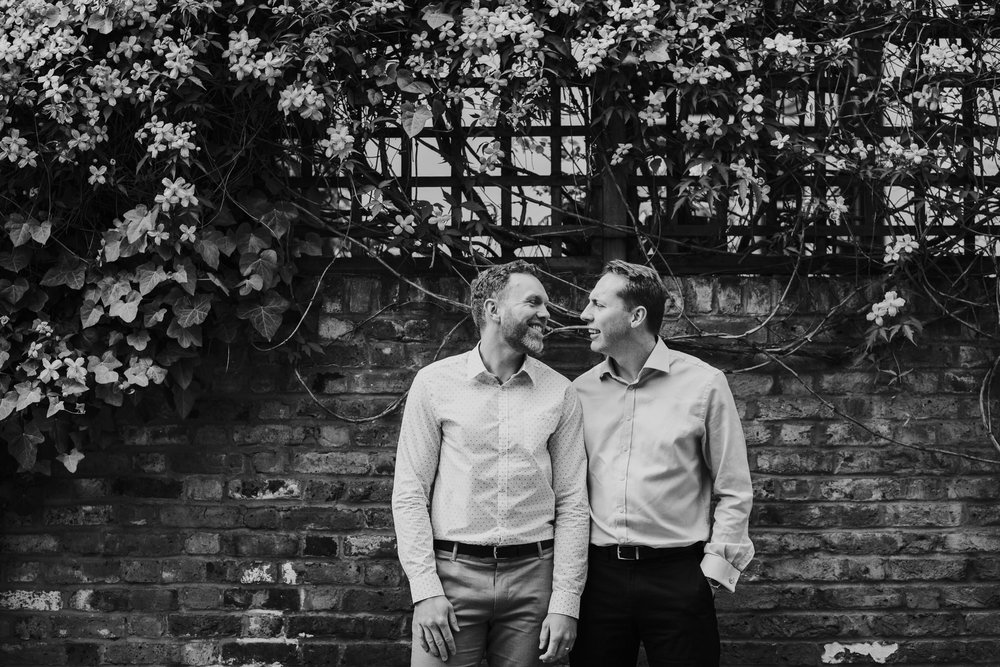 60 natural intimate moment between two gay grooms against brick wall.jpg