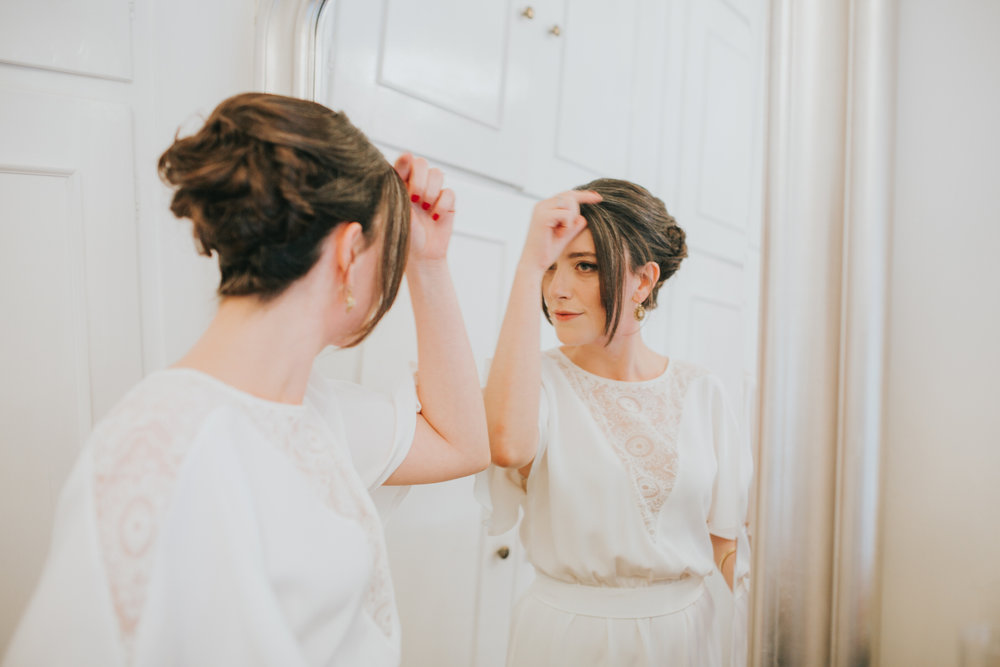 34-bride looking mirror getting ready Minna wedding dress.jpg