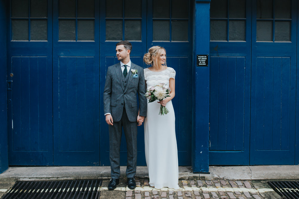 bride groom against industrial blue door Asia House wedding.jpg