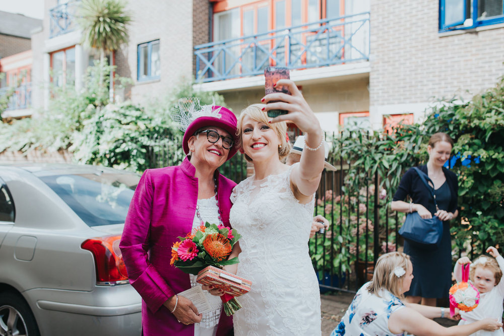 Bride taking a selfie with mother in magenta suit.jpg