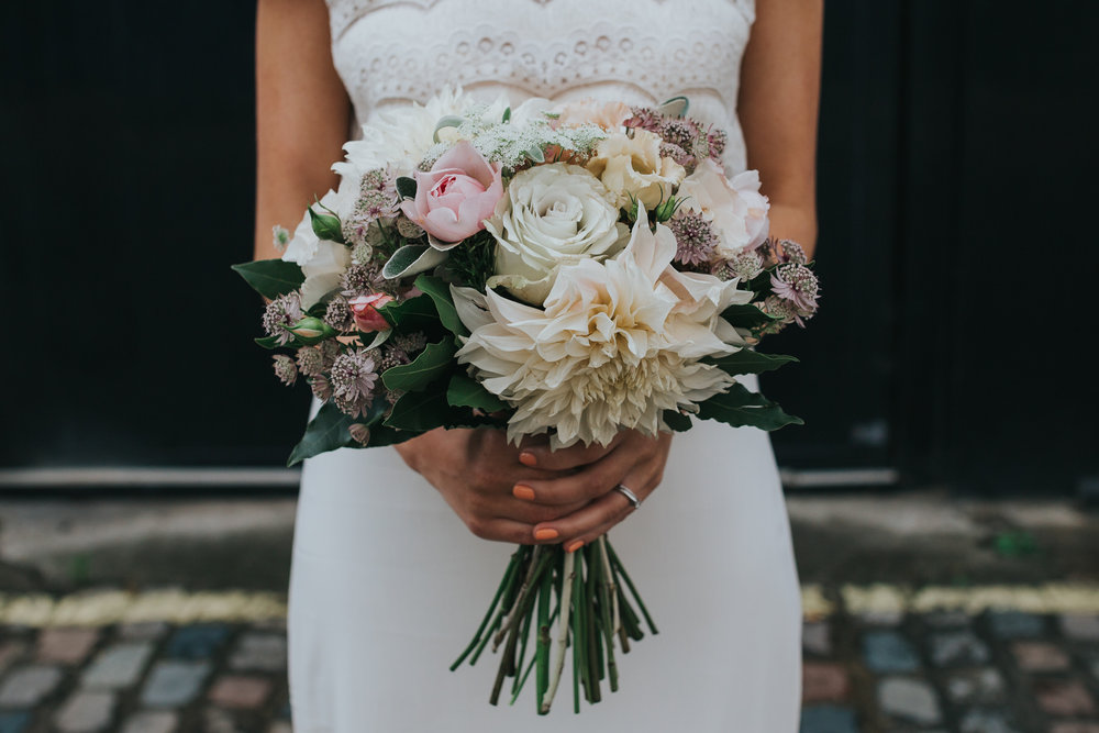 Bride holding large muted pink peach tone bouquet dahlia peonie roses .jpg