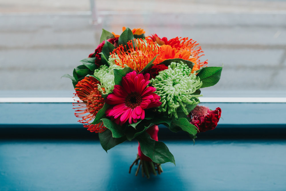 Bright orange pink wedding bouquet barberton daisies protea.jpg