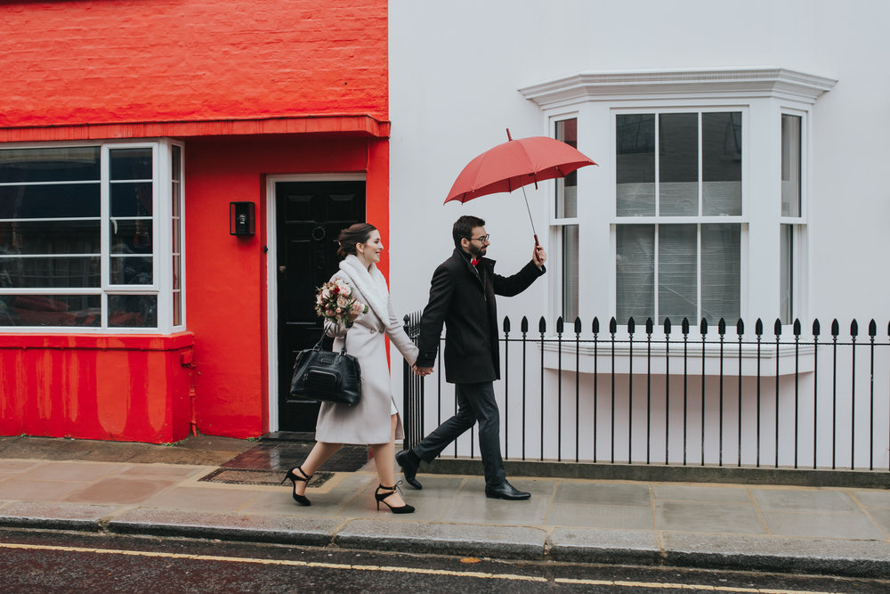 Chelsea streets wedding reportage groom red umbrella.jpg