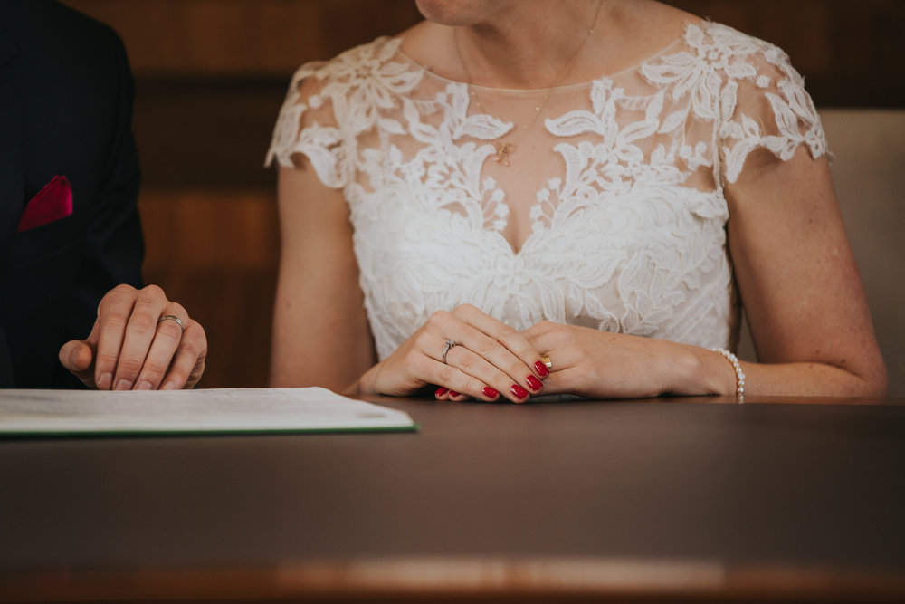 bride touching wedding ring signing register Stoke Newington Hall wedding.jpg