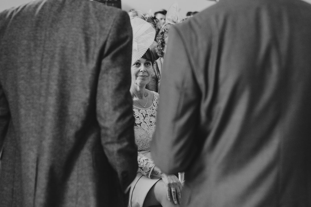 BW Asia House unposed documentary style wedding grooms mother peeking through.jpg