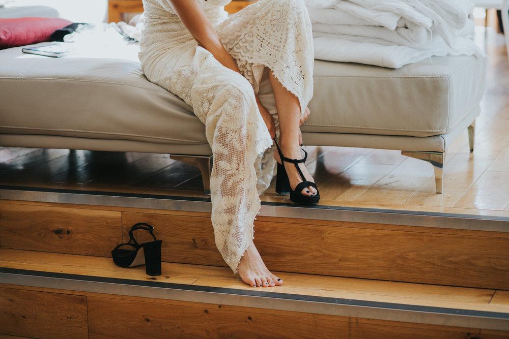 9 bride in crocheted wedding dress putting on black platform sandalsjpg.jpg