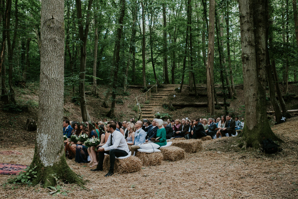 19 guest seated on hay bales at Paper Mill Woodland wedding East Sussex.jpg