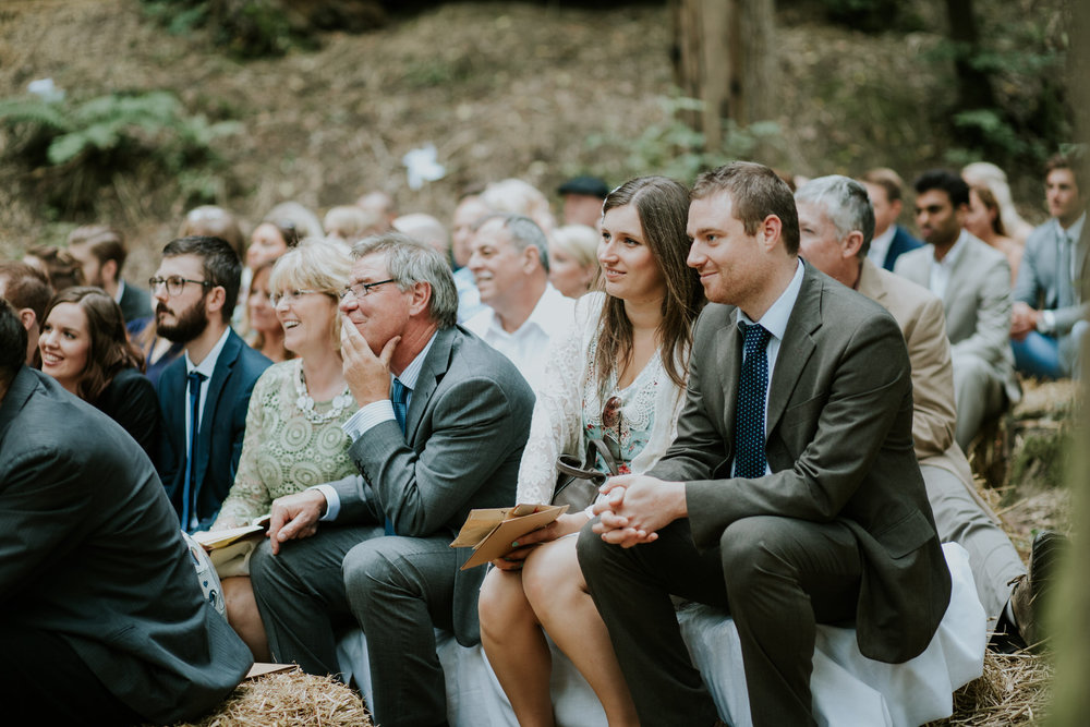 27 guests hay bales watching wedding ceremony East Sussex forest.jpg
