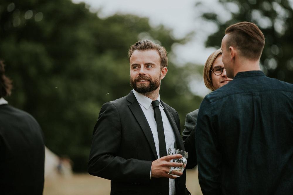 107 Kent woodland festival wedding guest drinking pints.jpg