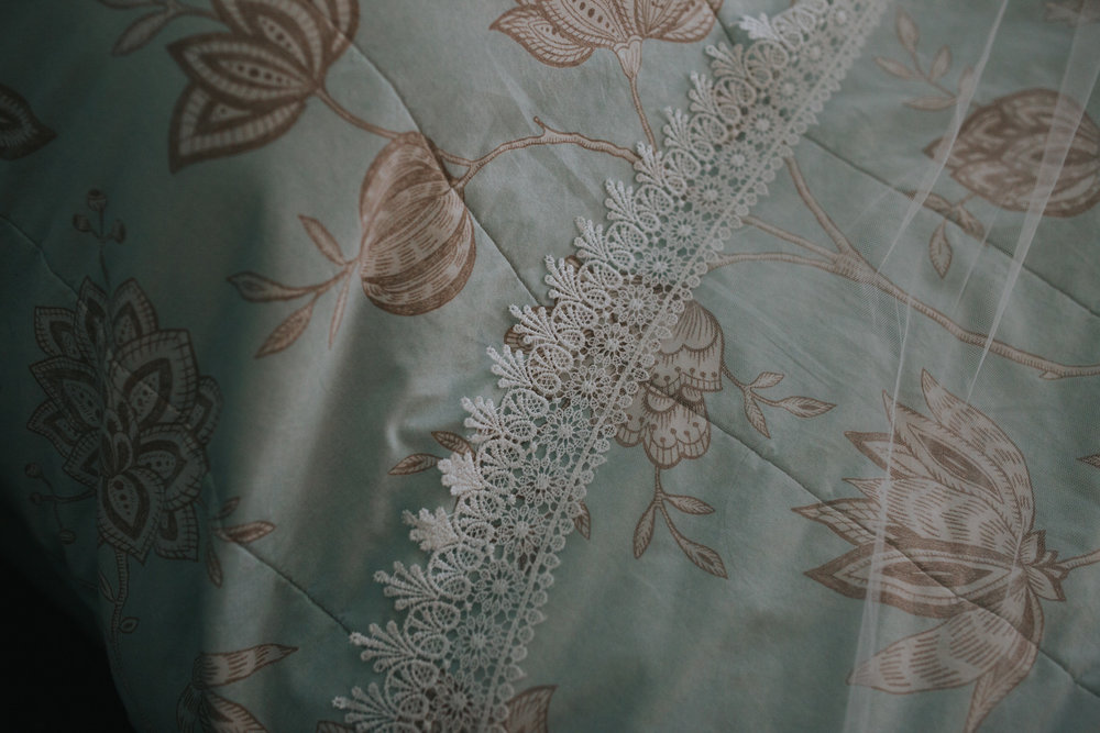 172 Wales wedding photography veil lace on floral bedspread.jpg