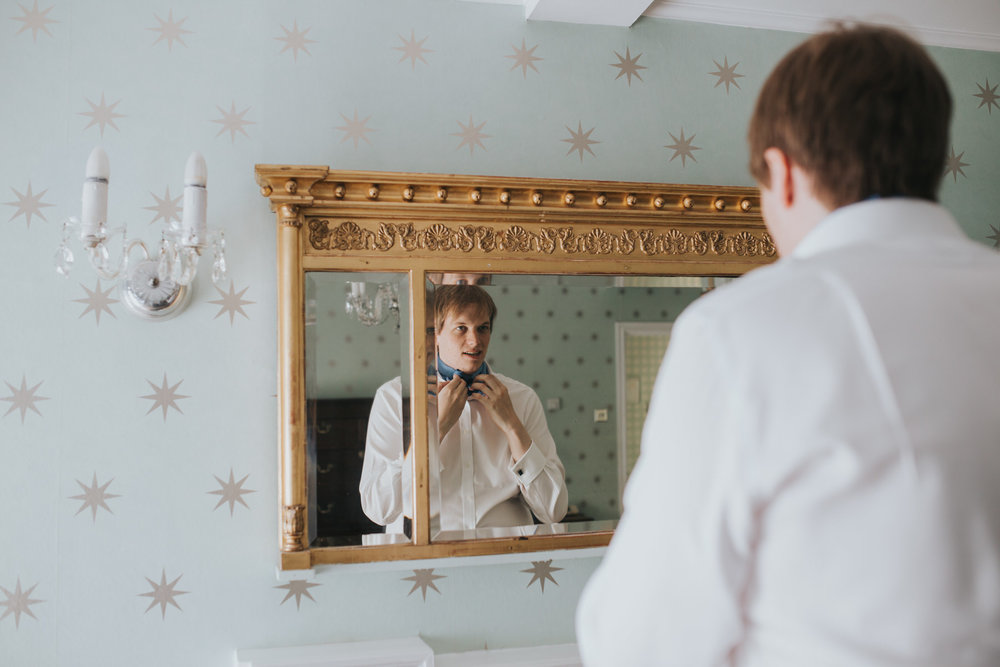 296 groom Gwilym tying cravat Portmeirion wedding.jpg