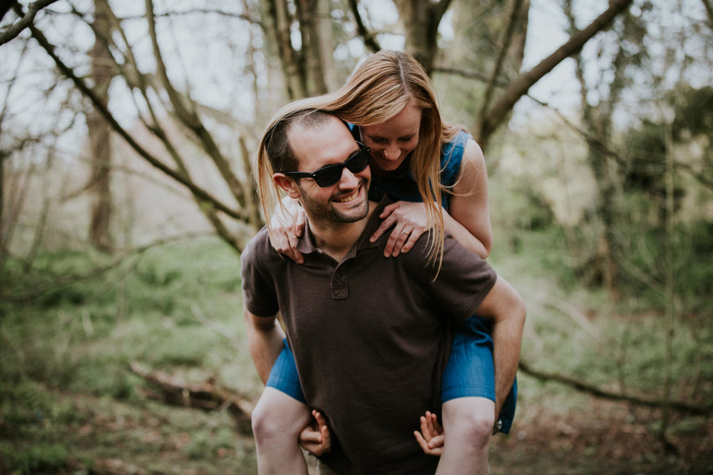 28-couple piggy back playing during couple portraits Richmond.jpg